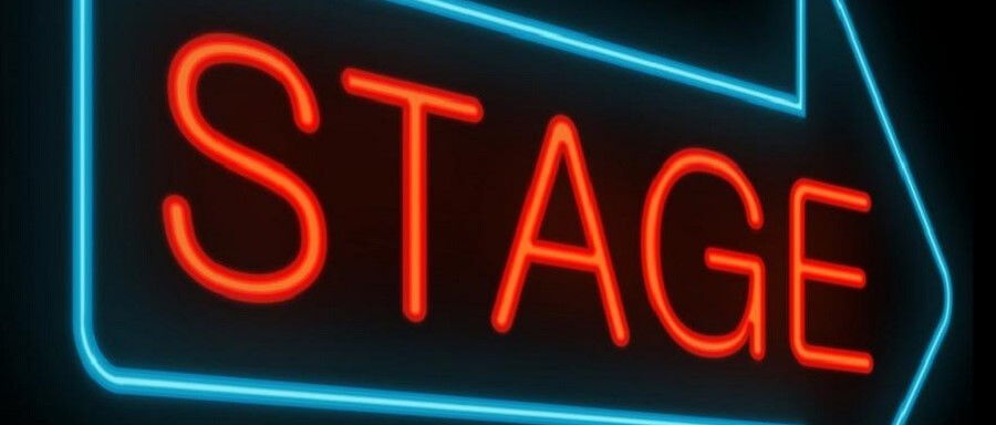 red stage sign in blue arrow on black background showing howto get to broadway auditions