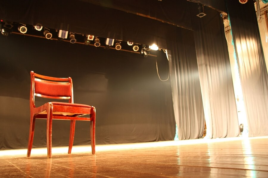 chair in the middle of a stage prepared for monologues