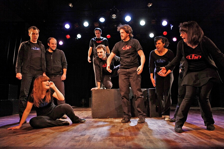 group of people demonstrating improv acting on a stage while having fun