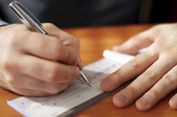 man writing a cheque on a desk