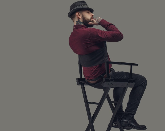 Man in hat sitting on film director's chair.