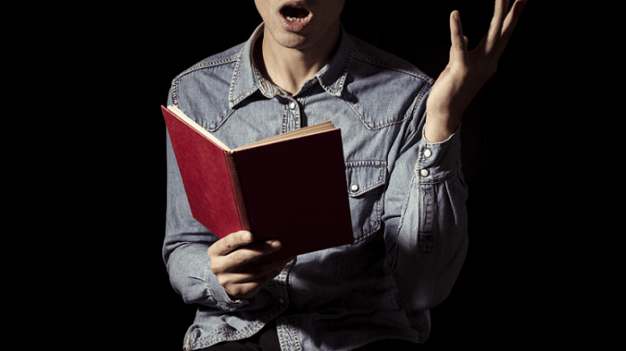 Close up of a man holding a book and reciting