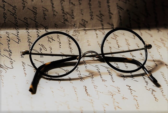 Pair of round glasses with black frame on a paper
