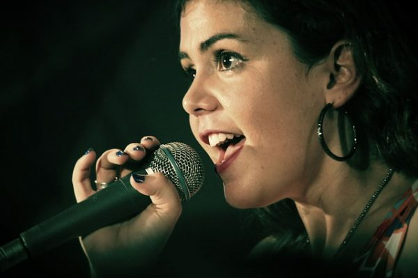 woman singing against black background