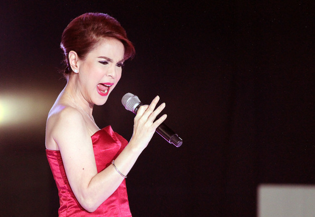 woman in red dress singing while holding a microphone